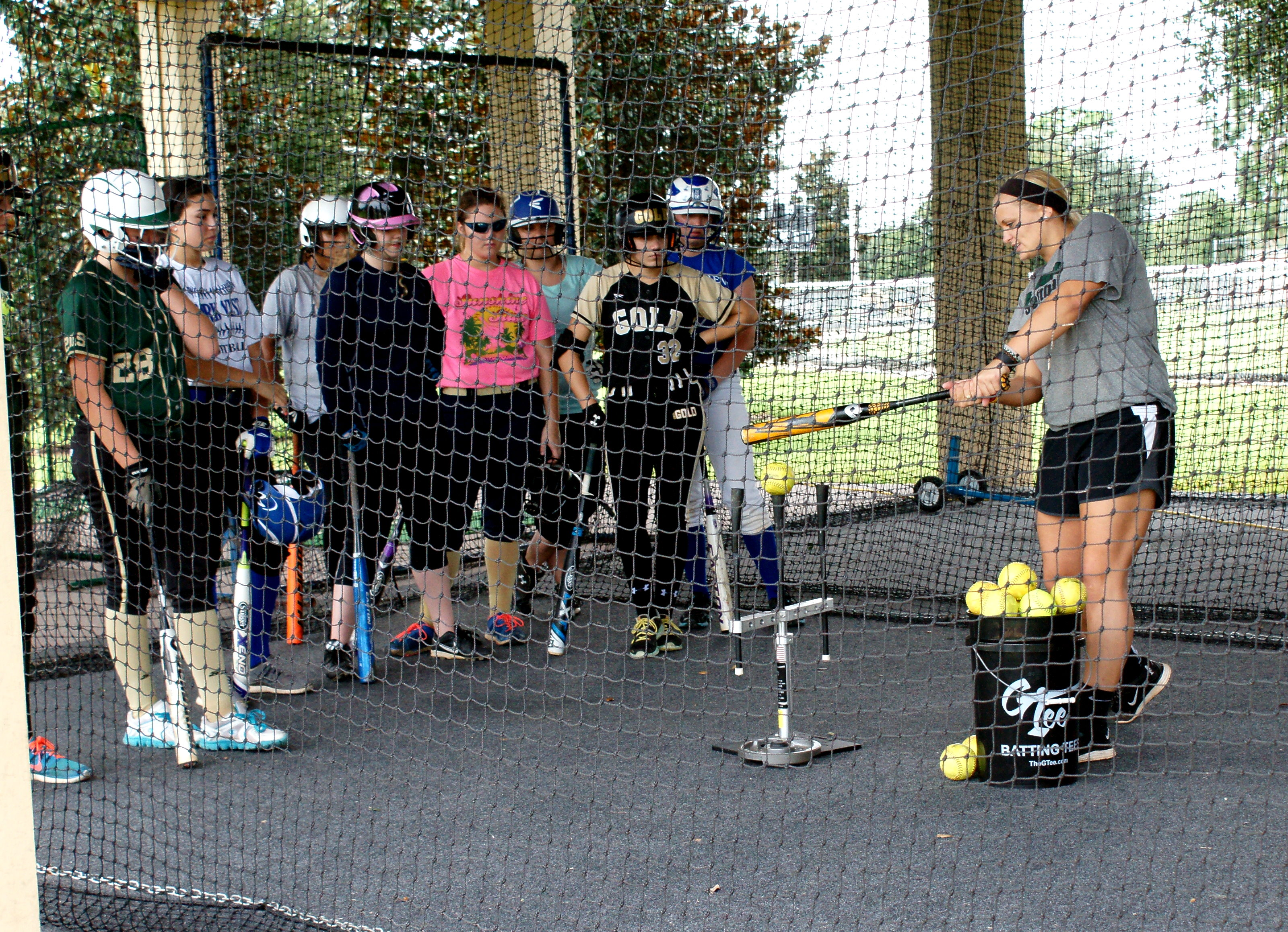 Former CF player Amy Szymanowski (L) shows softball players the correct way to hit